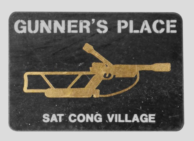Brass sticker for Gunner's Place at Sat Cong Village. Sticker photographed off of Bob Fowlie's tackle tool box.