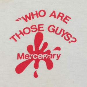 "Close up crop on back side of ""Who Are Those Guys?"" shirt logo."