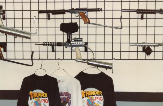 """Thunder Pig T-Shirts on the wall under a nelson framed Carter Comp and a """"Rolling Thunder"""" engraved Buzzard that likely belongs to Fernando Castillo. Photo from the archives of Ted Hines."""